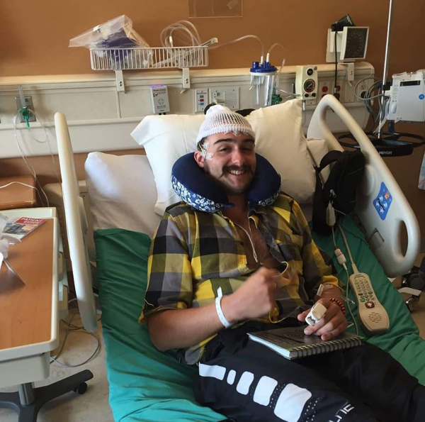 Kyle Parker recovers in a hospital bed after brain surgery.