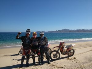 Three dirt bike riders pause their ride for a photo on the beach.