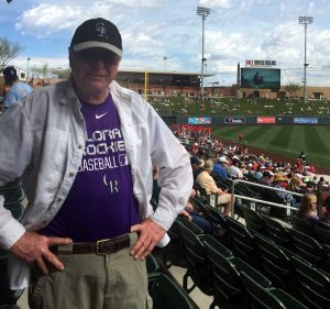 Jim in the stands of spring training wearing a Colorado Rockies Baseball shirt