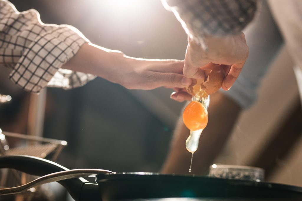 A person cracks an egg into a skillet.