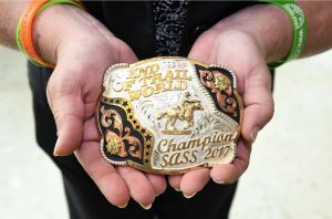 Kidney transplant recipient Sara Millard holds her rodeo belt buckle.
