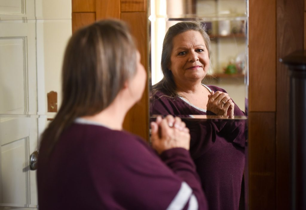 A formerly blind woman looks into a mirror to see her own face.