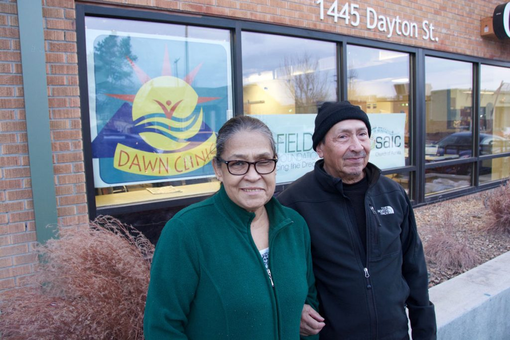 a couple poses outside the DAWN Clinic in Aurora