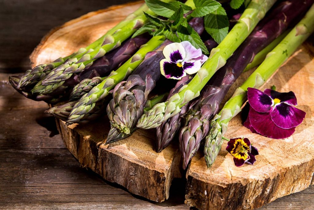 purple and green asparagus arranged with edible flowers on a wooden platform