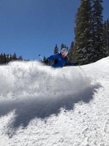 Kristina Mitchel sprays snow while skiing in this photo.