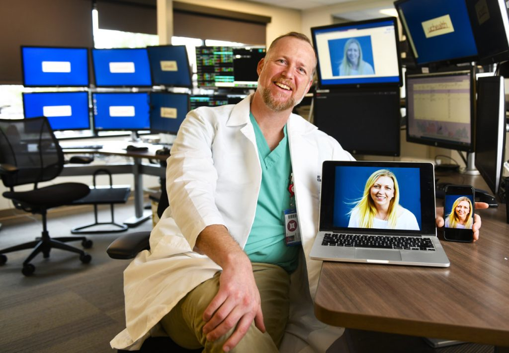 Portrait of Dr. Chris Davis with computer screens and a portrait of a patient during a Virtual Visit.