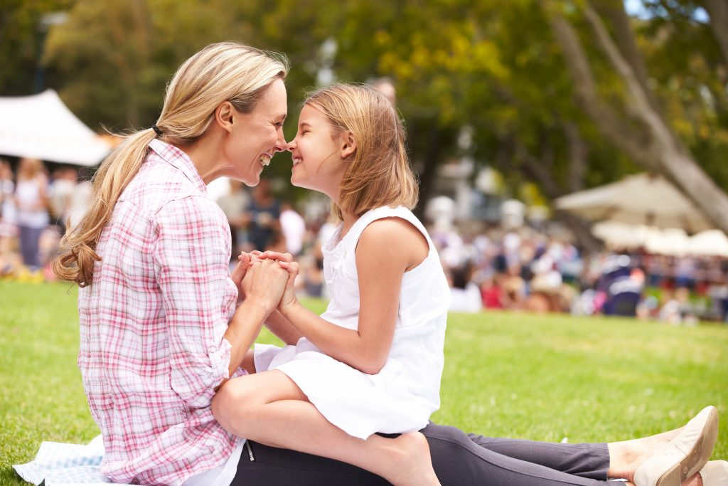 A mom and daughter smile at each other in a park.