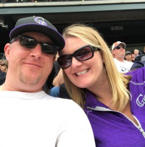 A couple smiles for a selfie at a Colorado Rockies game.