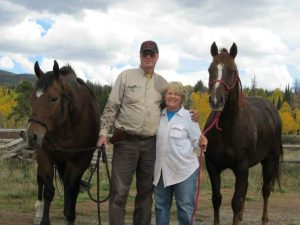 Bob Bryant and Connie Kassel stand side by side between two horses.