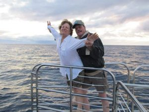 """In this photo, Connie Kassel and Bob Bryant reenact the iconic """"I'm Flying!"""" scene from the movie Titanic while on a boat in Hawaii."""