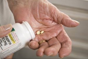 An older person takes baby aspirin.
