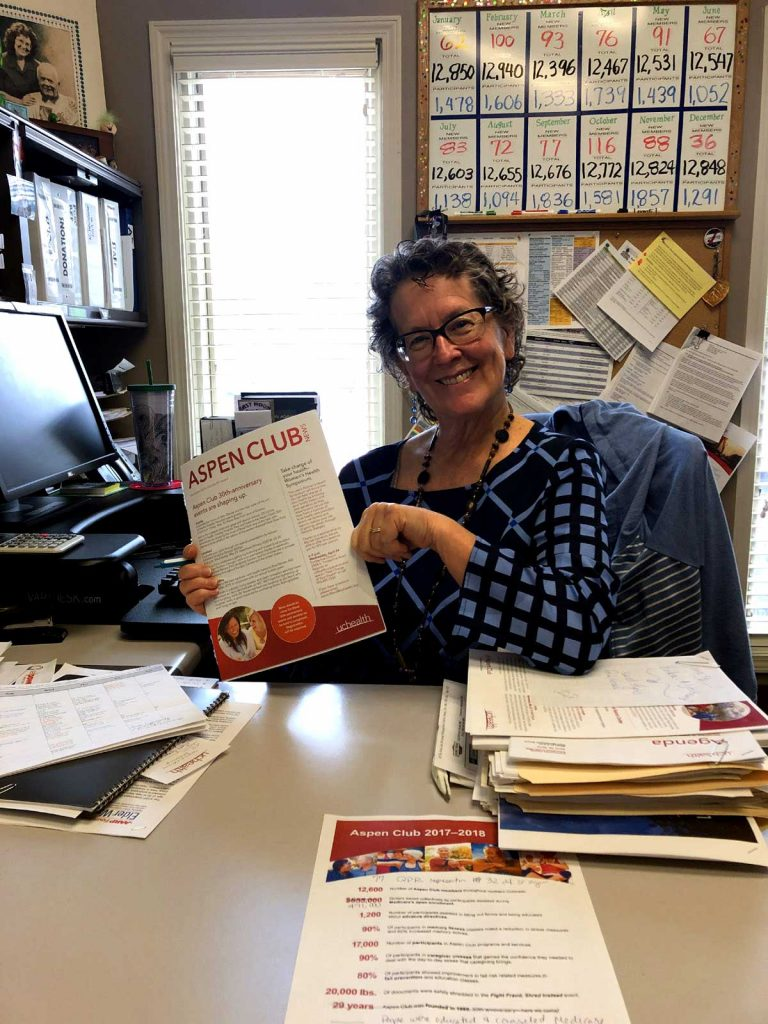 Jill holds up an aspen club newsletter while sitting in her office
