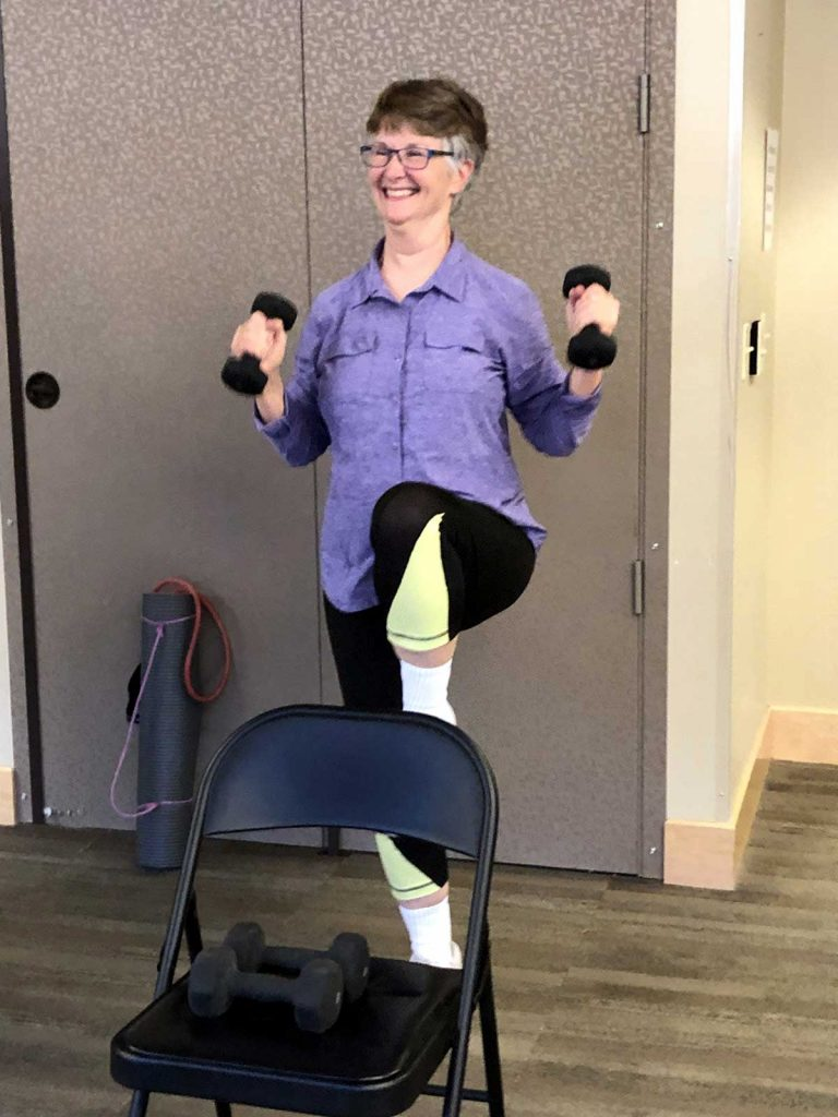 woman holding weights while lifting her leg
