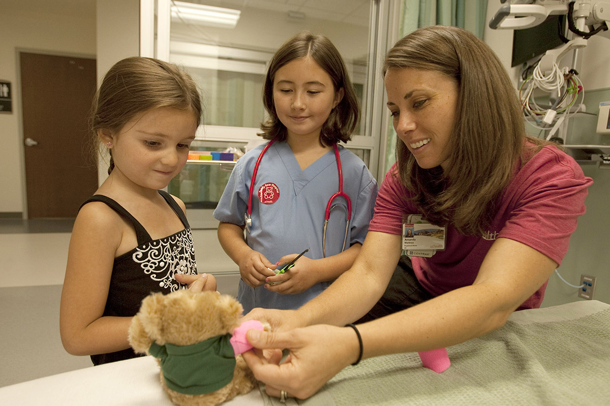 A nurse bandages up a stuffed bear as two young girls watch.