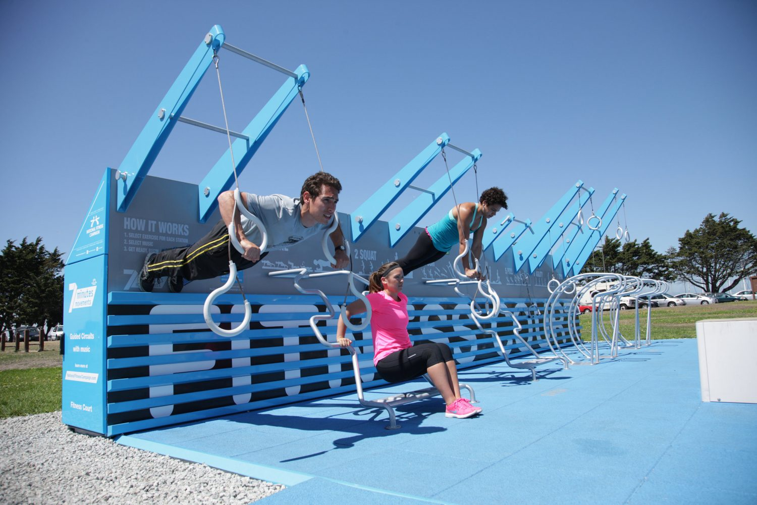Three people are shown working out on outdoor fitness court.