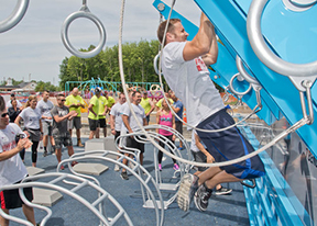 Man does chinups on exercise equipment during a competition at outdoor fitness court.