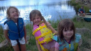 Girls giggle as they were their lifevests near a lake.