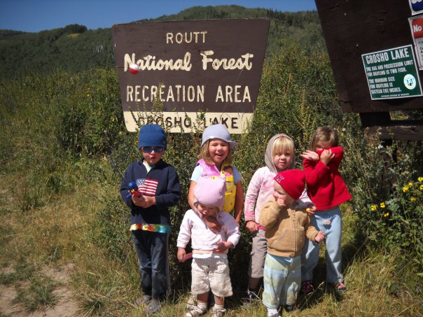 Kid campers pose in front of a Forest Service sign near Steamboat