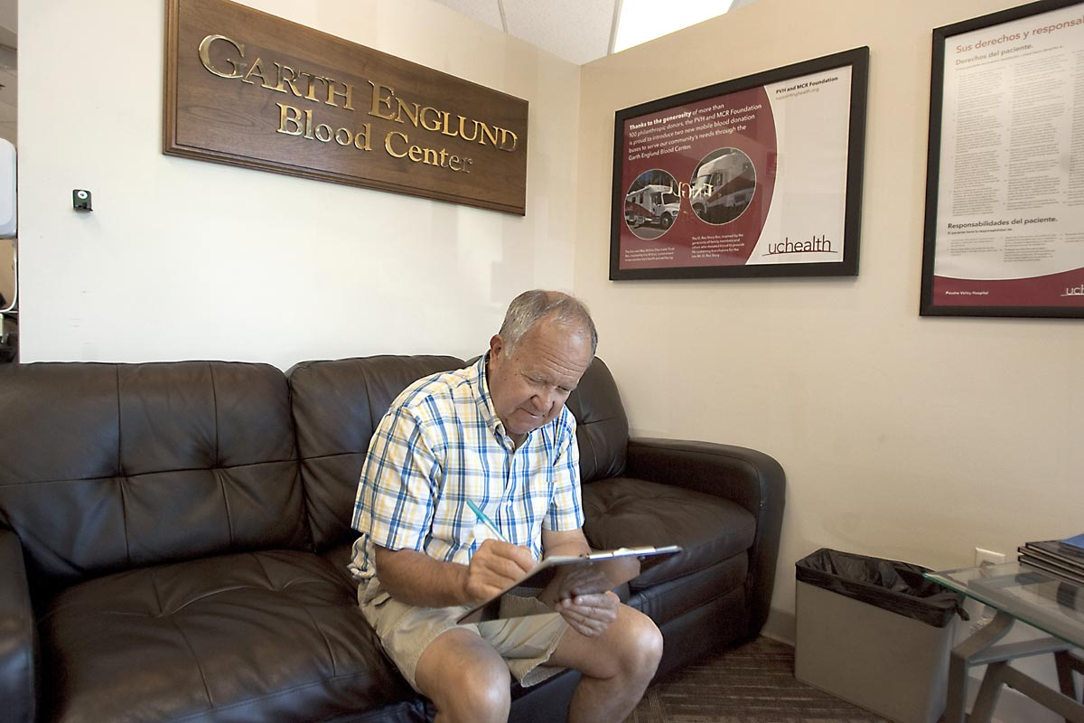 Simon fills out paperwork on the couch at the blood donation center.