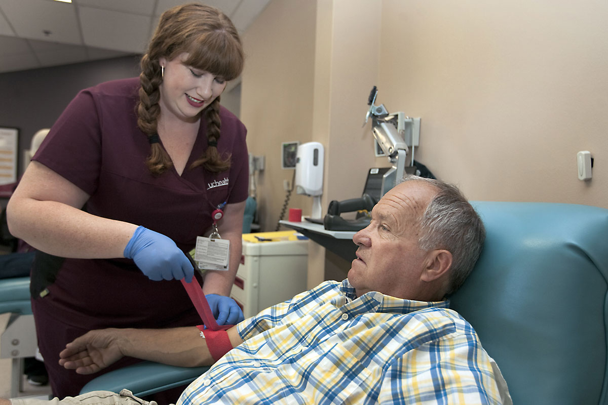 phlebotomist ties off patient's arm after blood donation