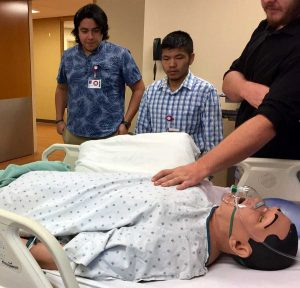 students stand by a patient simulation dummy