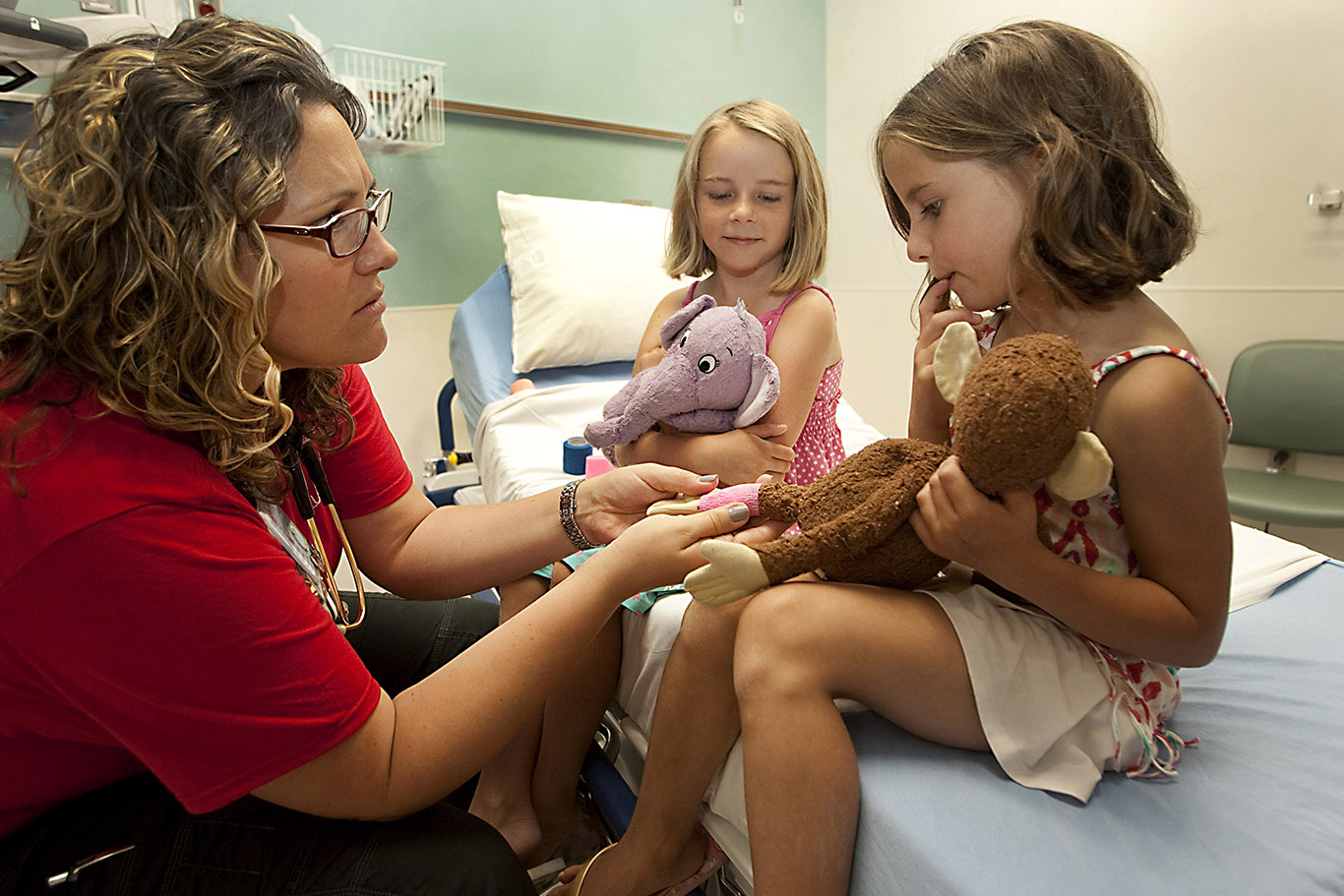 Two girls hug their stuffed animals as a nurse pretends to tend to the stuffed animals' injuries.