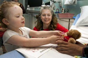 Child reaches for teddy bear.