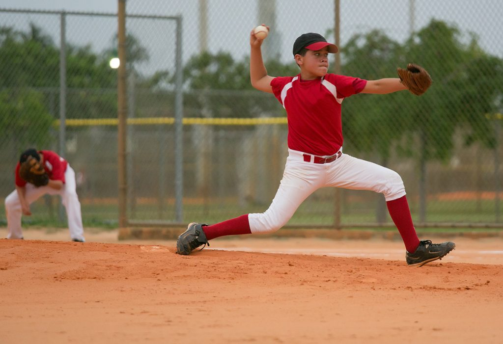 A young boy pitches a baseball during a game in this photo.