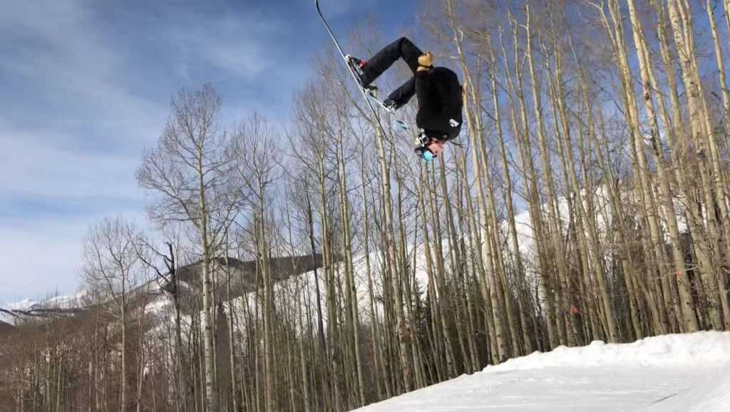 A young man does a back flip on skis