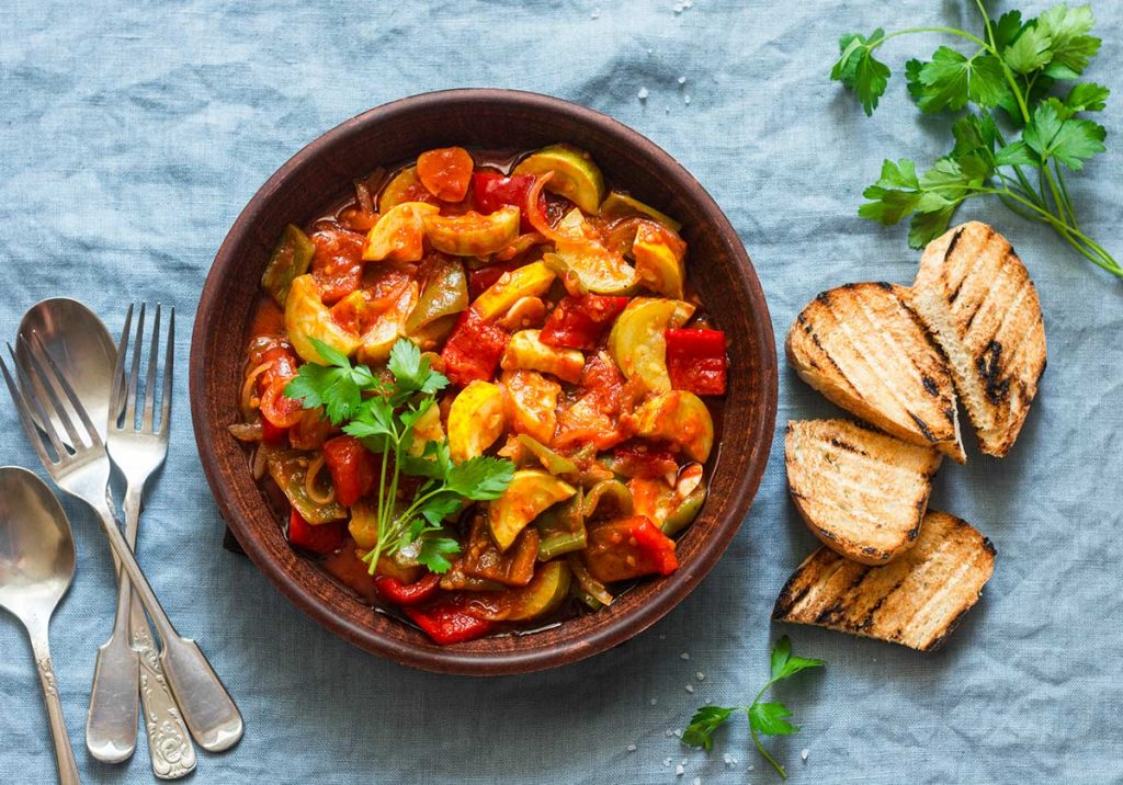 a bowl of ratatouille with silverware and roasted bread