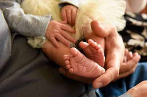 a baby's feet peak out of a gold tutu