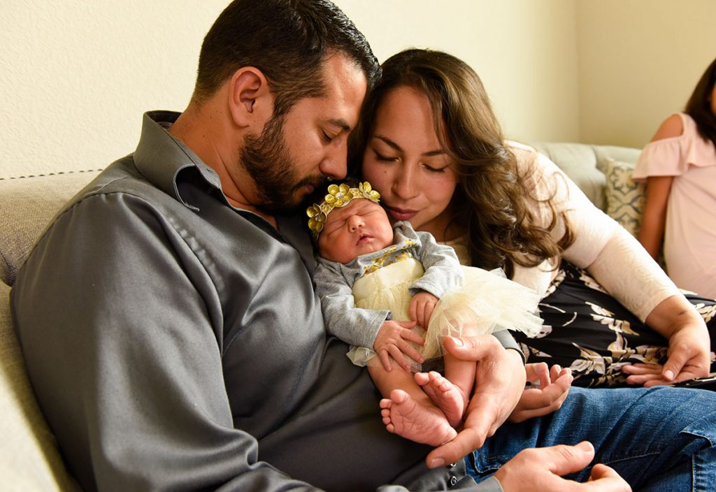 A couple kisses their newborn daughter.