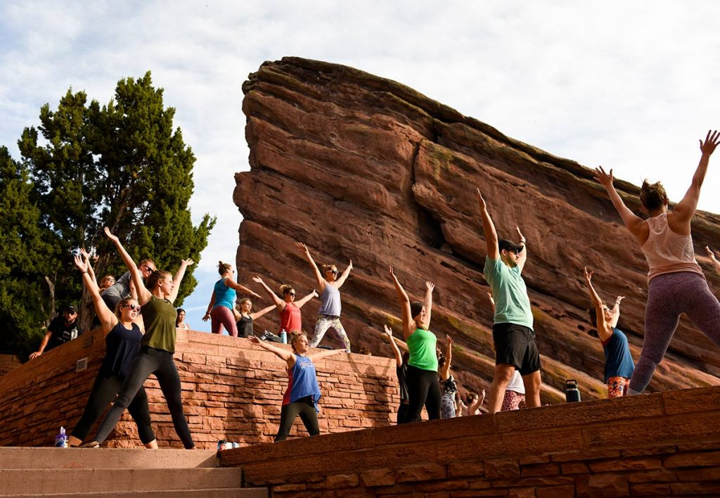 People doing yoga raise their arms at Red Rocks Amphitheater