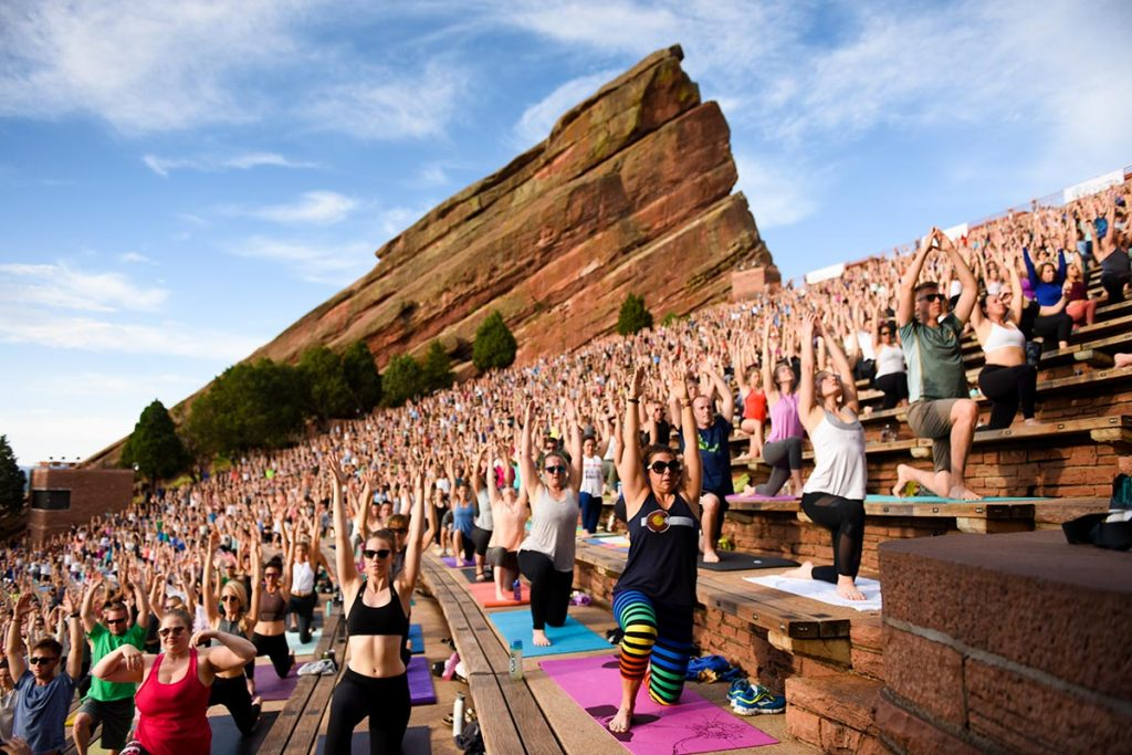 Hundreds of people doing yoga at Red Rocks Amphitheater