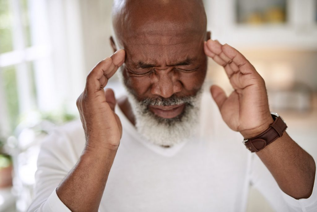 A man holds his temples, as if having a severe headache