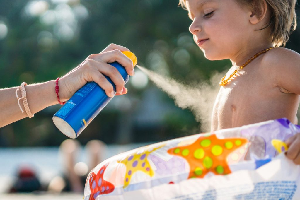 A photo of a child being sprayed with sunscreen.