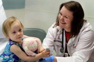 ER pharmacy director smiles at little girl in the ER
