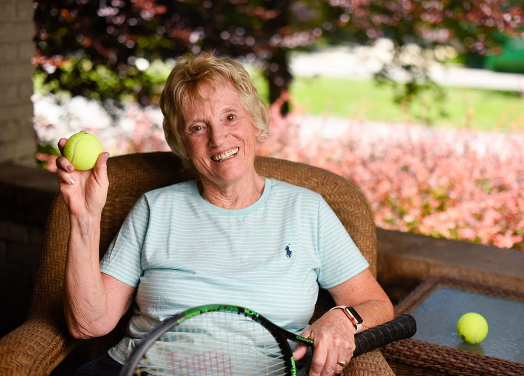 Susan High suffered a torn hamstring while playing tennis. She poses on her front porch in Denver with a tennis ball and racket.