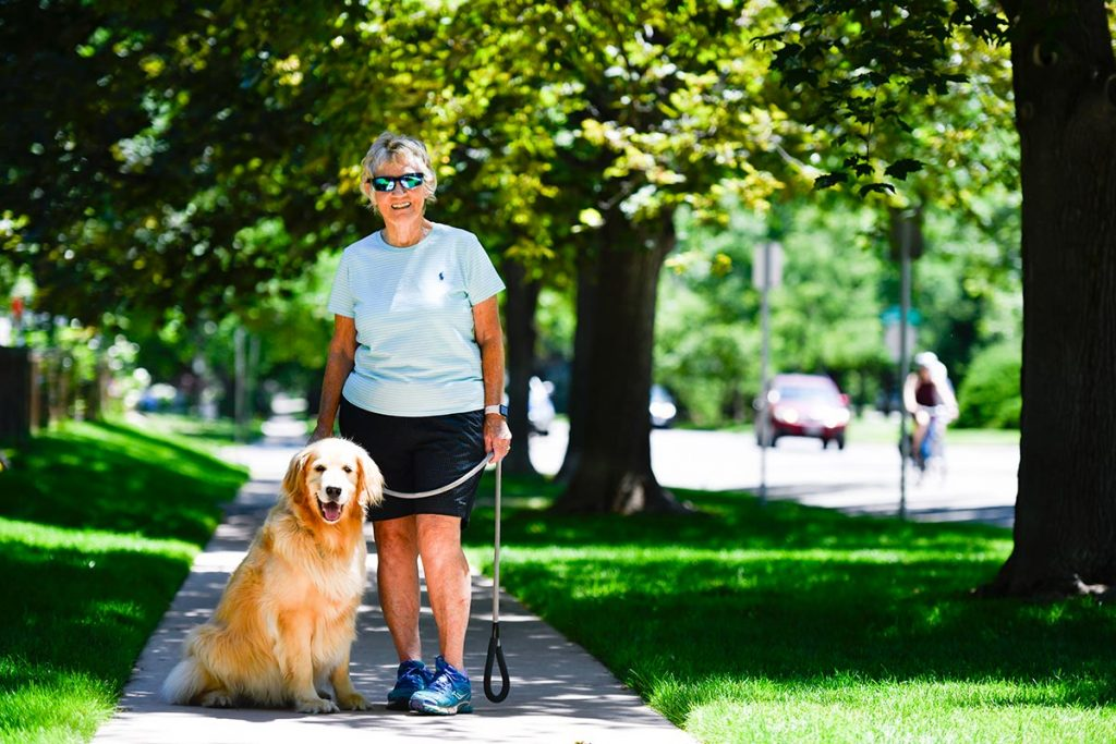 71-year-old athlete Susan High poses with her golden retriever