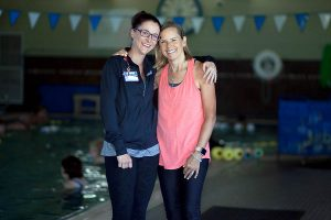 two women stand together by pool