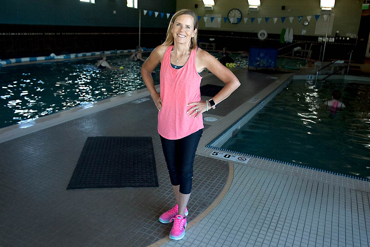 women stands by pool where she does classes to overcome cancer related fatigue