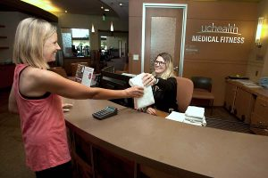 receptionist hands women a towel at the front desk