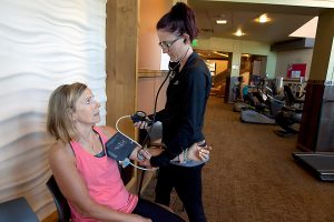 Therapist takes blood pressure of patient in the gym.