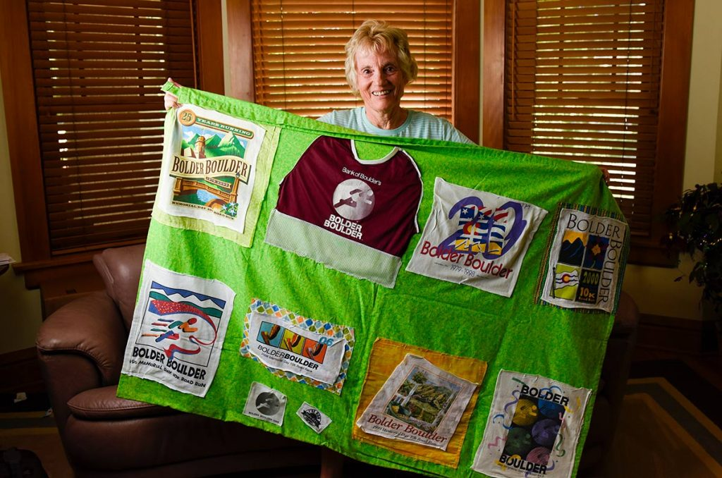 Runner Susa High poses with a quilt a friend made her. It features Boulder Bolder tee-shirts from the 41 races she's completed.
