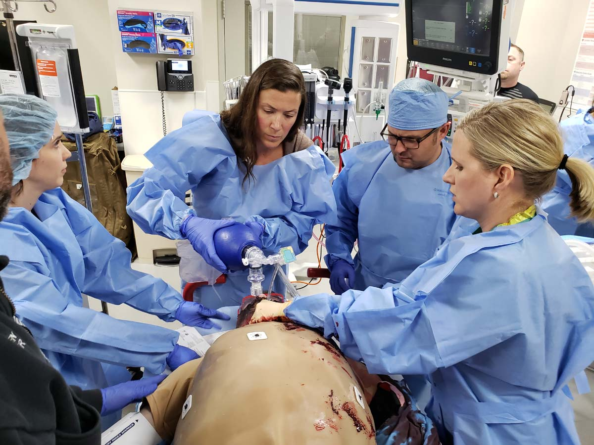 Health professionals participate in a training simulation involving a cut suit.
