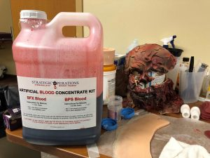 A large jug of fake blood and a blast mask, worn to simulate an explosion-related injury, are among cut suit parts.