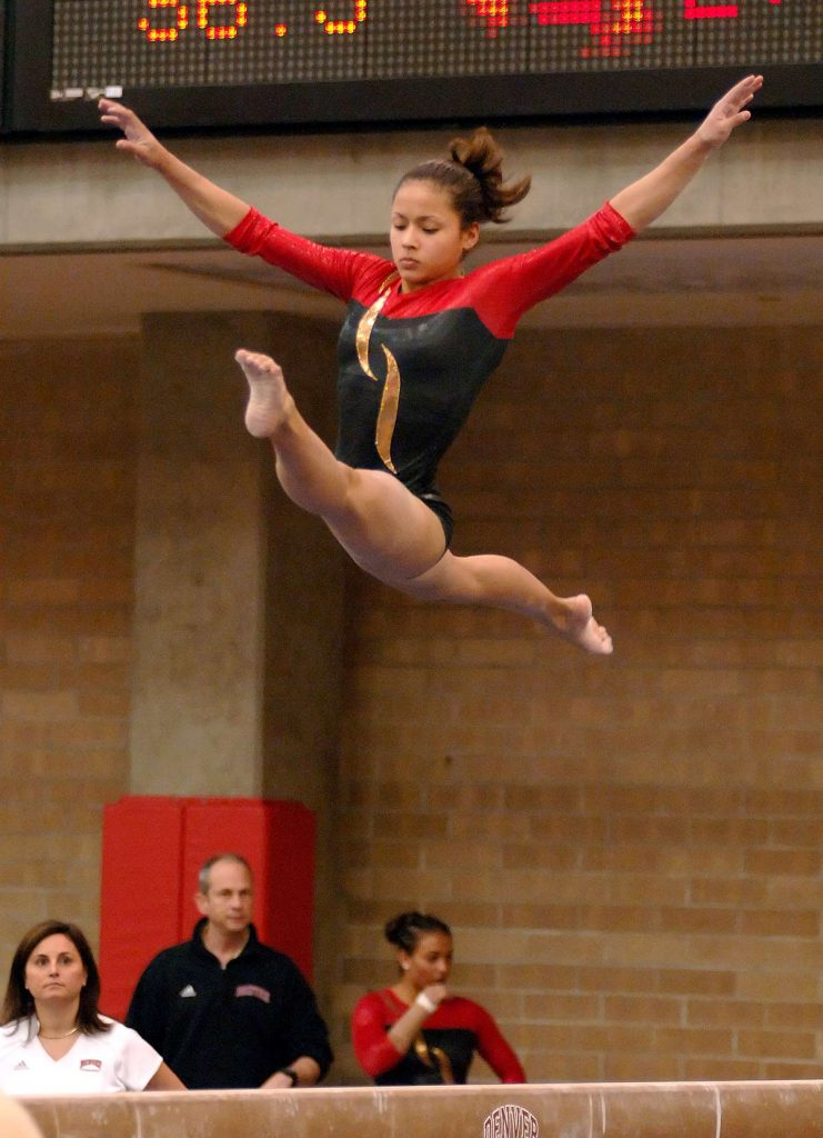 Olympic gymnas, Jessic López, does the splits on the balance beam while competing for the University of Denver.