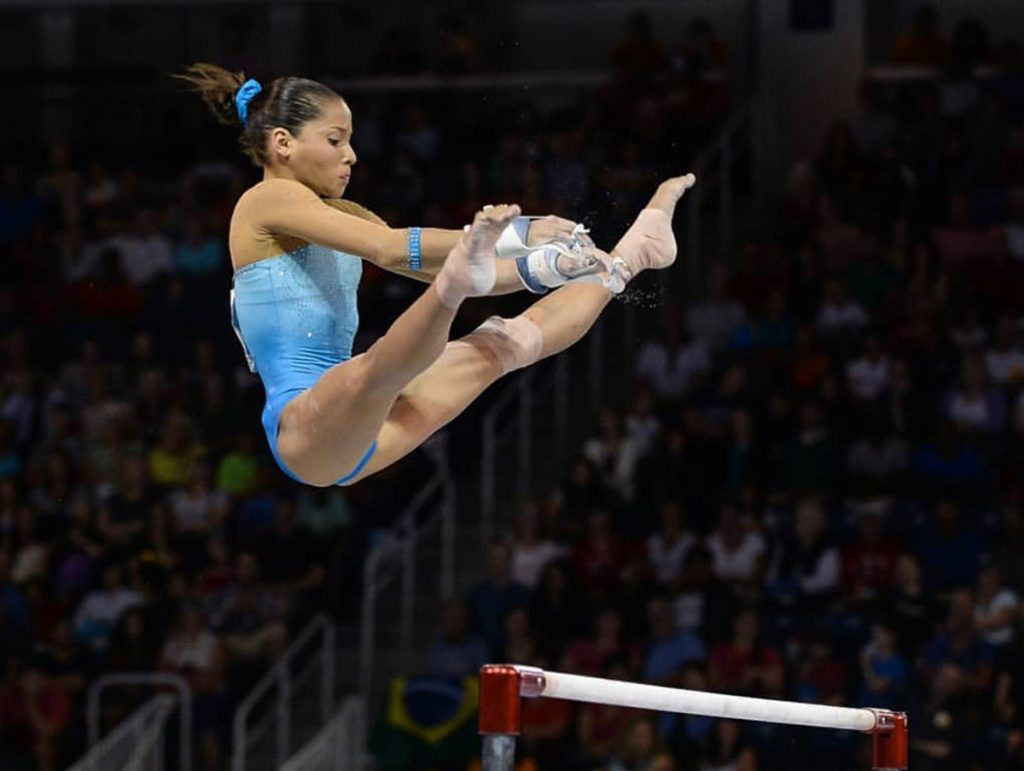 Olympic gymnast Jessica López does the splits in mid-air during a routine on the uneven bars