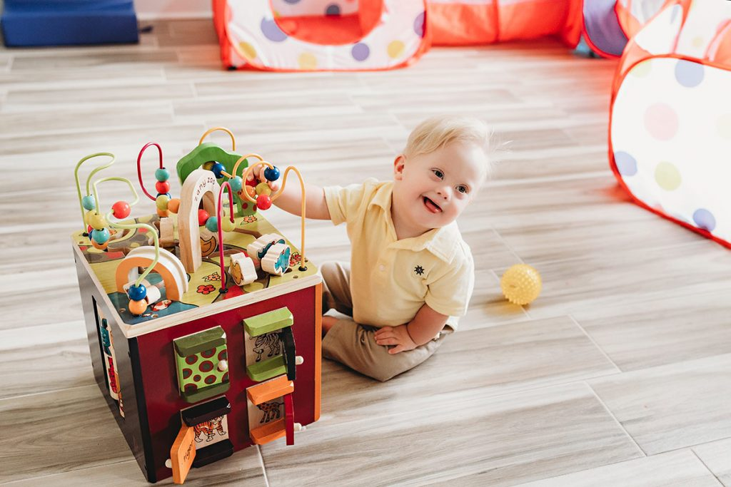 Depite heart problems in utero, little Hudson Hartman is cheerful and doing well. Here, he plays with his toys.