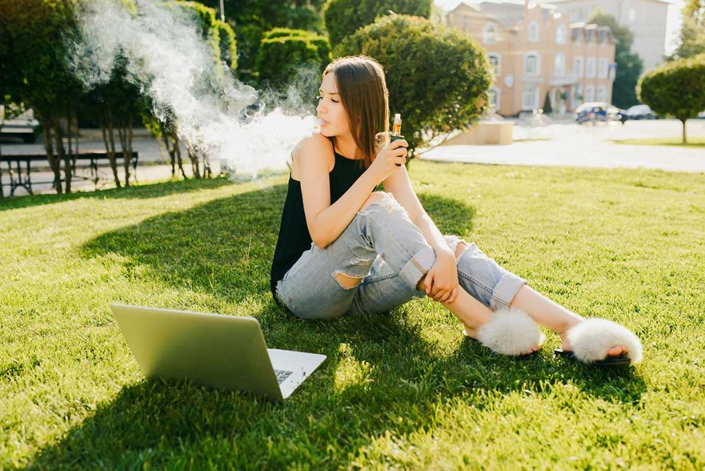 a photo of a young woman smoking an e-cigarette